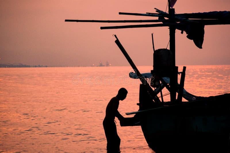 Siluet av fiskaren Preparing His Boat för att fiska på skymning Tid arkivbild