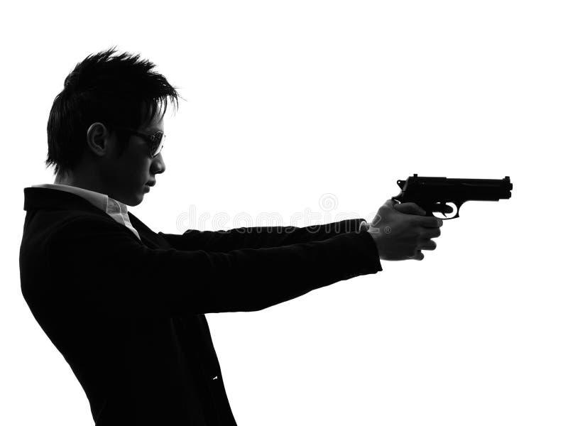 Silueta asiática del tiroteo del retrato del asesino del pistolero imagenes de archivo