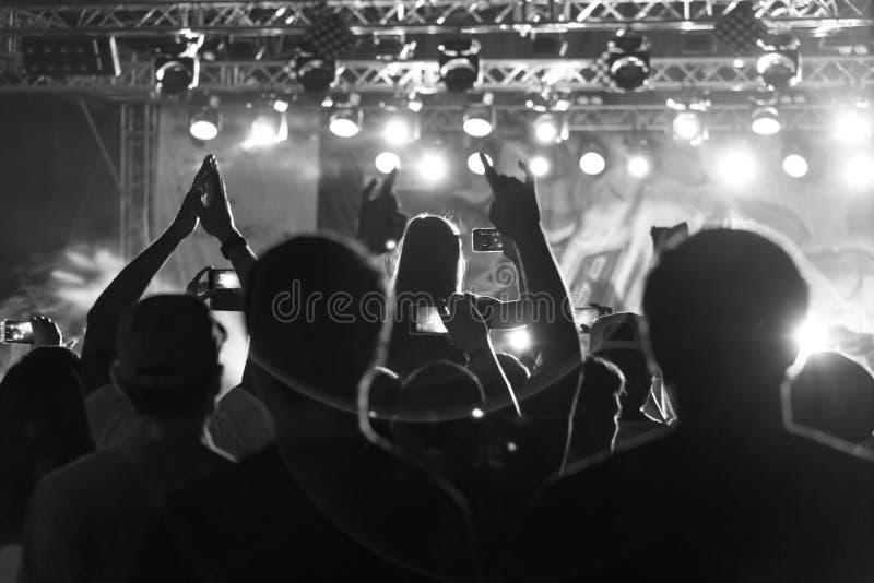 Silueta blanco y negro de la gente en muchedumbre en un festival de música Concierto con la gente de baile derecha retroiluminada fotos de archivo