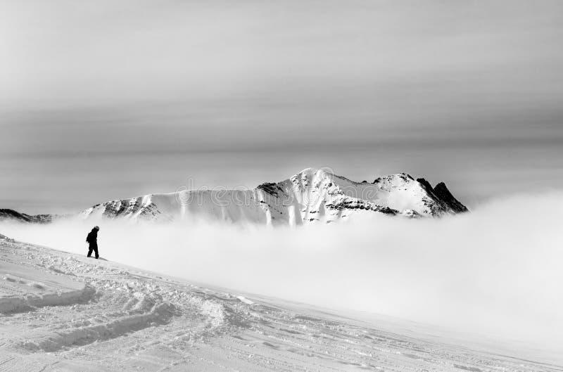 Silueta blanco y negro del snowboarder en ingenio fuera de pista de la cuesta imagen de archivo