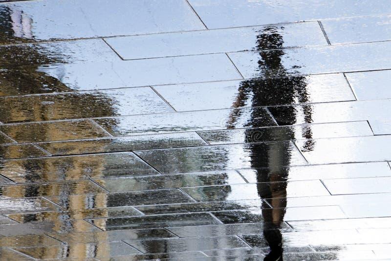 Silueta borrosa de la reflexión de un stree mojado de la ciudad de la persona que camina imágenes de archivo libres de regalías