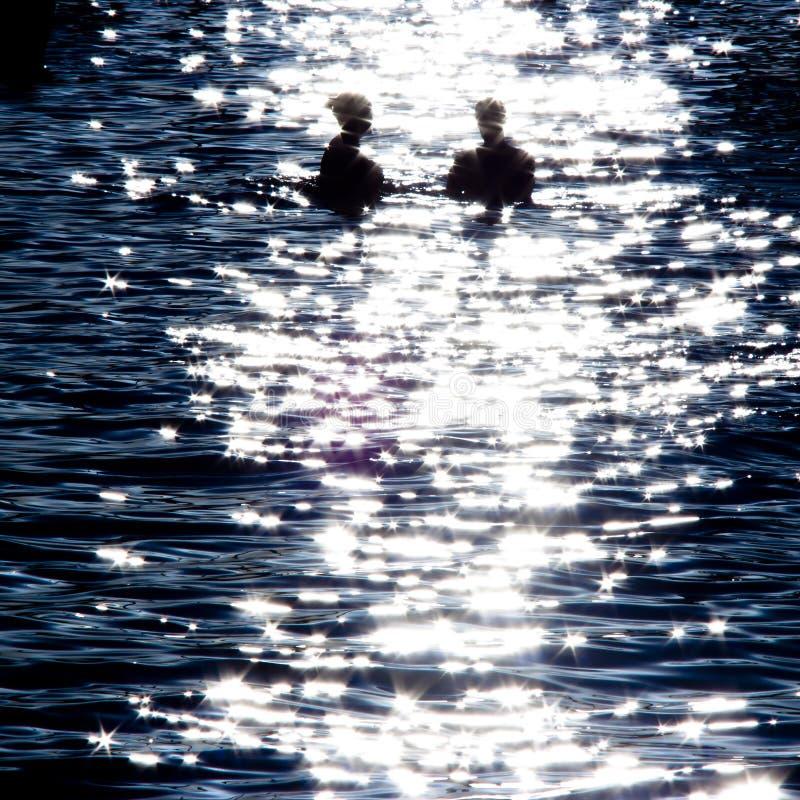 Silueta borrosa de un par en el mar del claro de luna fotos de archivo