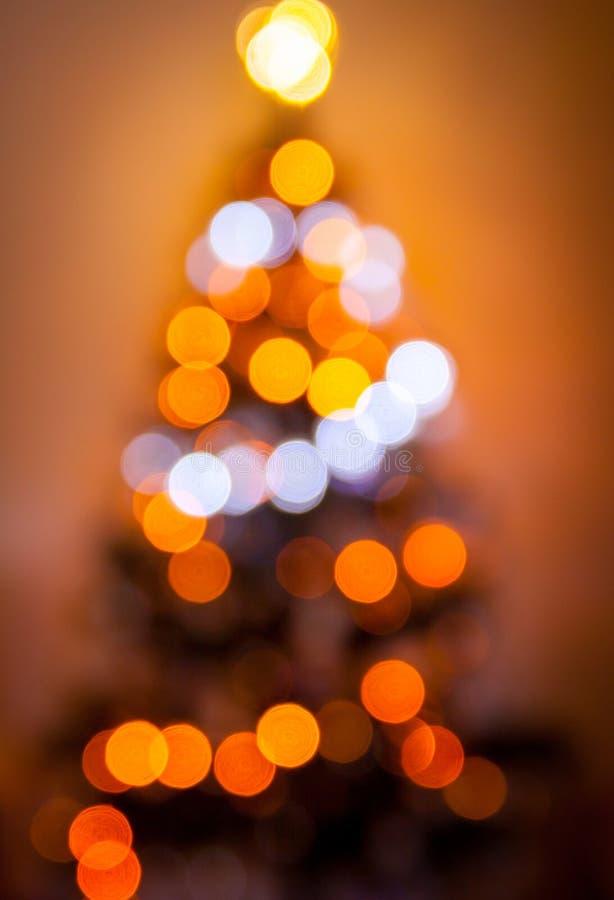 Silueta borrosa Defocused del árbol de navidad con las luces borrosas en fondo caliente fotos de archivo libres de regalías
