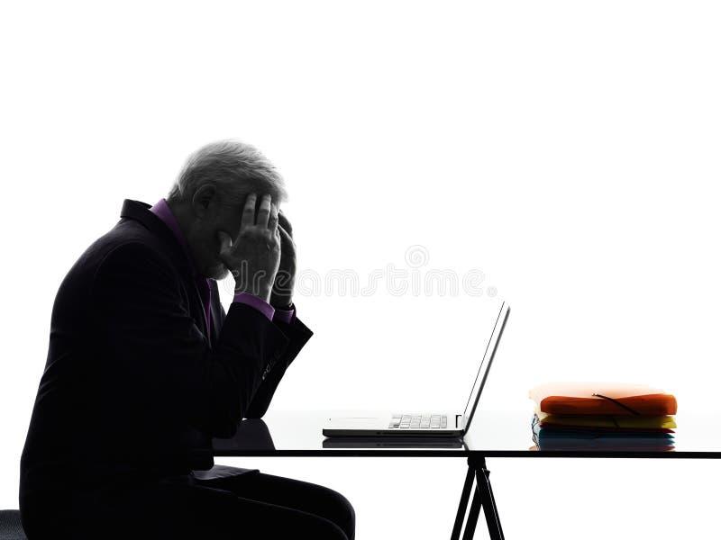 Silueta cansada computacional mayor del dolor de cabeza del hombre de negocios fotos de archivo