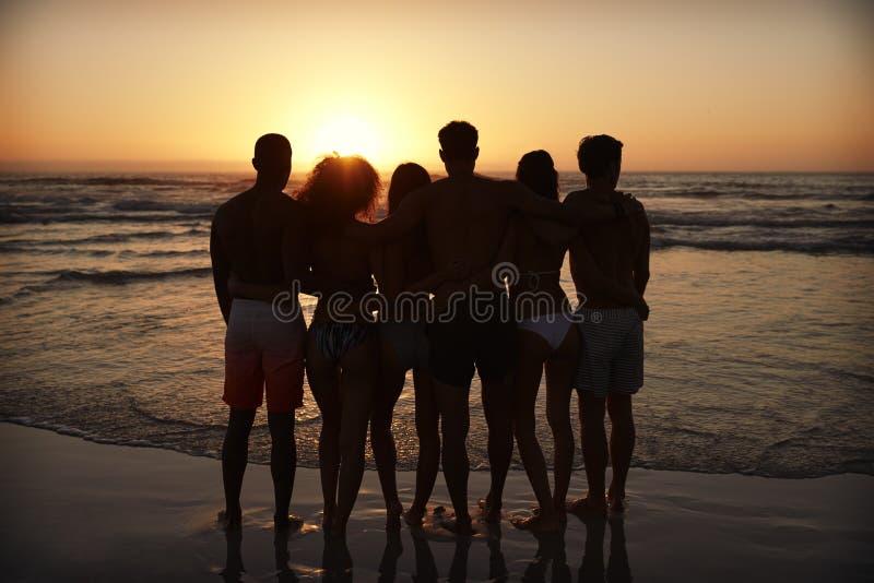 Silueta de amigos en puesta del sol de observación de las vacaciones de la playa sobre el mar imagen de archivo libre de regalías