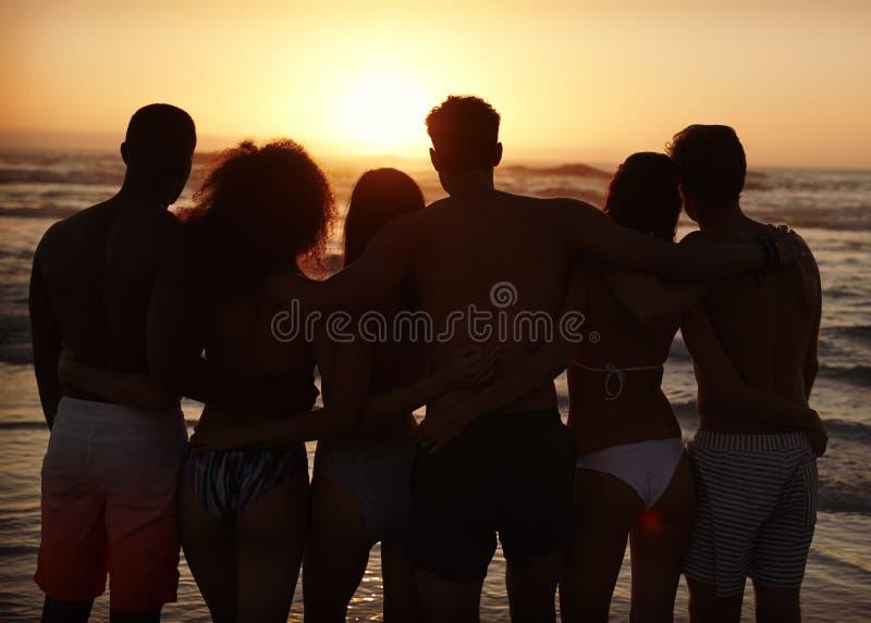 Silueta de amigos en puesta del sol de observación de las vacaciones de la playa sobre el mar fotografía de archivo libre de regalías
