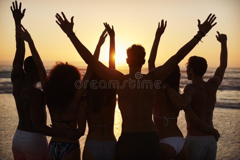Silueta de amigos en puesta del sol de observación de las vacaciones de la playa sobre el mar fotos de archivo