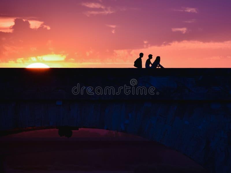 Silueta de amigos jovenes en una puesta del sol colorida al volver el hogar, cruzando un puente fotos de archivo