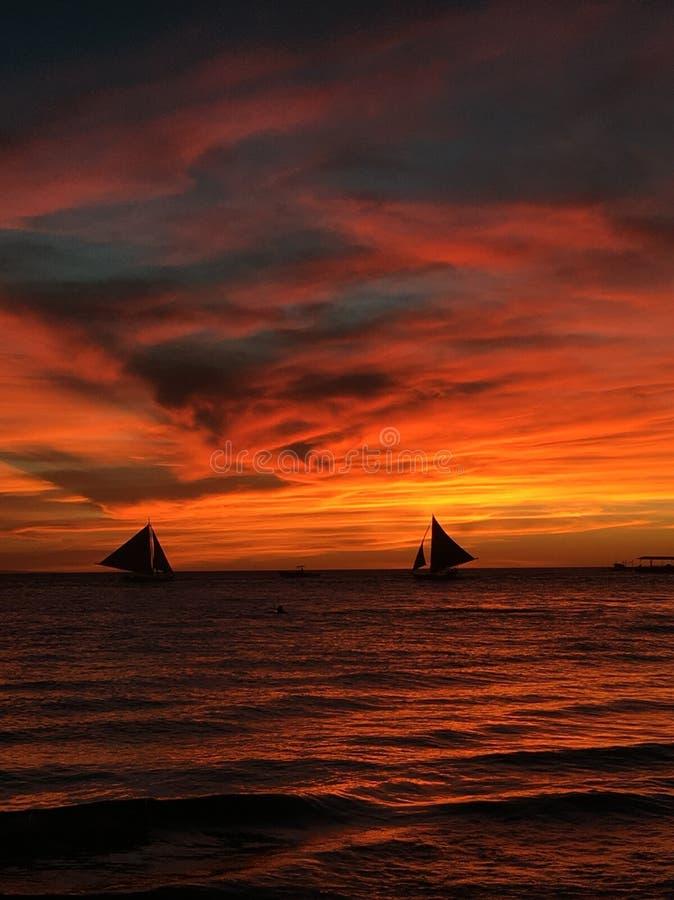 Silueta de barcos en la puesta del sol imagen de archivo