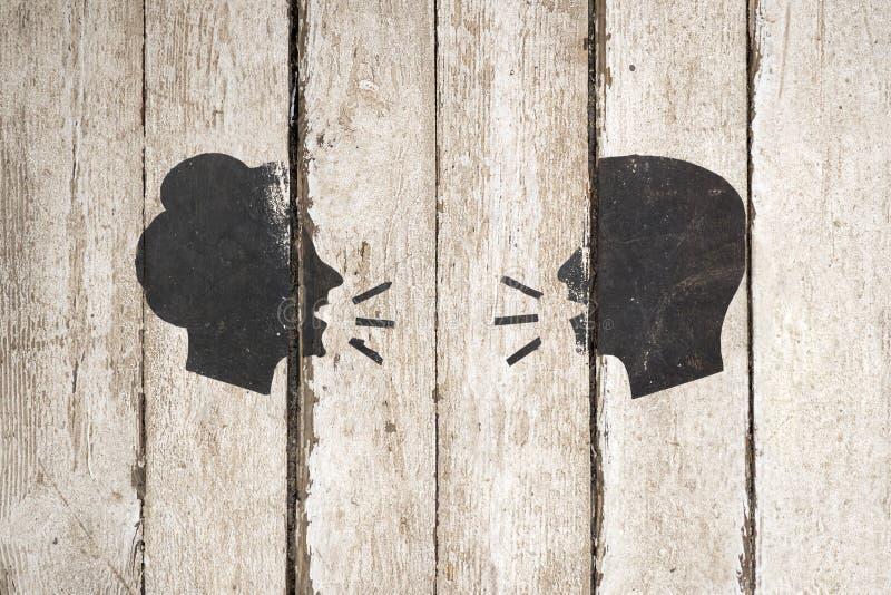 Silueta de discurso de la gente en fondo de madera Ejemplo del icono de la conversaci?n del hombre y de la mujer aislado en blanc imagen de archivo libre de regalías