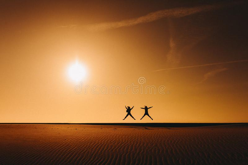 Silueta de dos amigos de las mujeres que saltan en la playa en la puesta del sol durante hora de oro Diversión y amistad al aire  imagenes de archivo