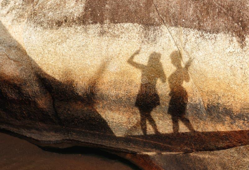 Silueta de dos figuras femeninas en una piedra grande en día soleado del verano imágenes de archivo libres de regalías