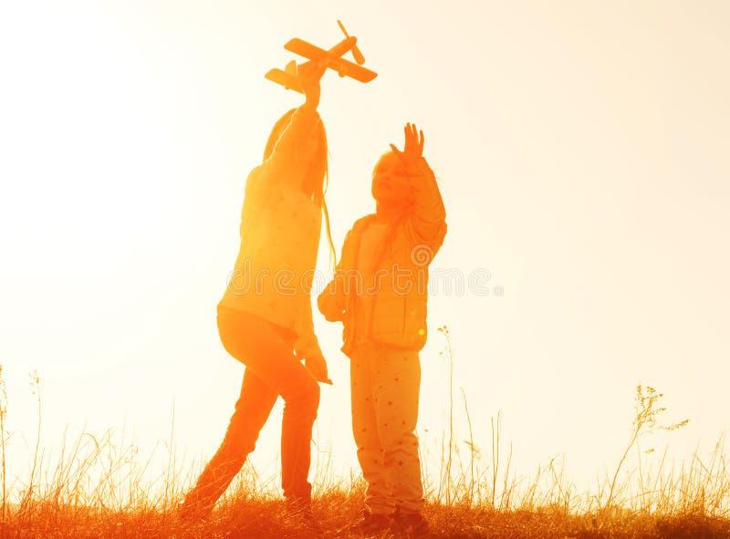 Silueta de dos hermanas que juegan con el juguete del aeroplano en la puesta del sol foto de archivo