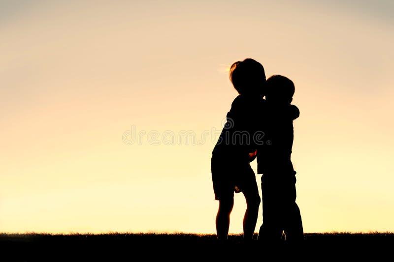 Silueta de dos niños jovenes que abrazan en la puesta del sol foto de archivo