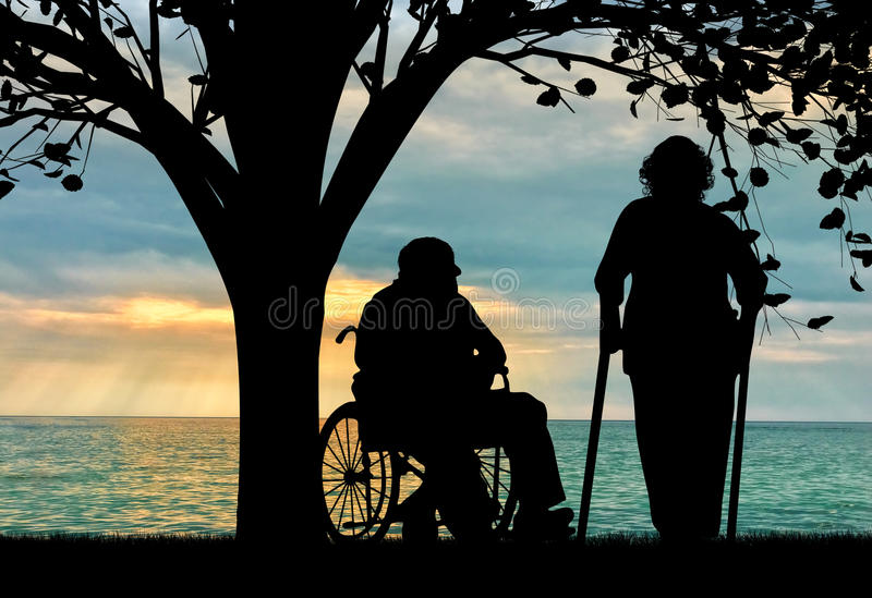 Silueta de dos personas con discapacidades fotografía de archivo