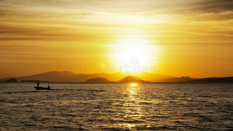 Silueta de dos pescadores en un pequeño barco de pesca con el motor externo en el océano en el anochecer con puesta del sol anara imagen de archivo libre de regalías