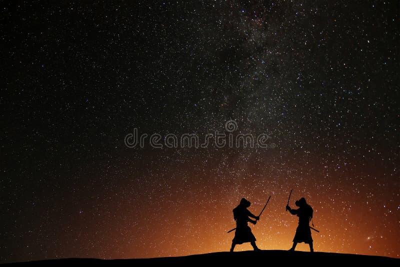 Silueta de dos samurais contra el cielo estrellado foto de archivo libre de regalías