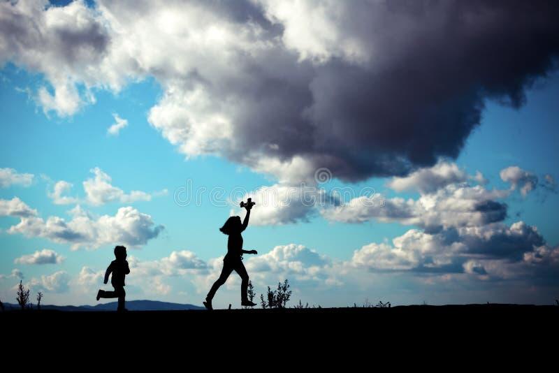 Silueta de jugar a niños imagen de archivo libre de regalías