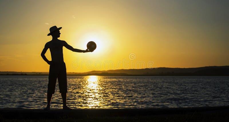 Silueta de la bandera del hombre en la puesta del sol imagen de archivo libre de regalías
