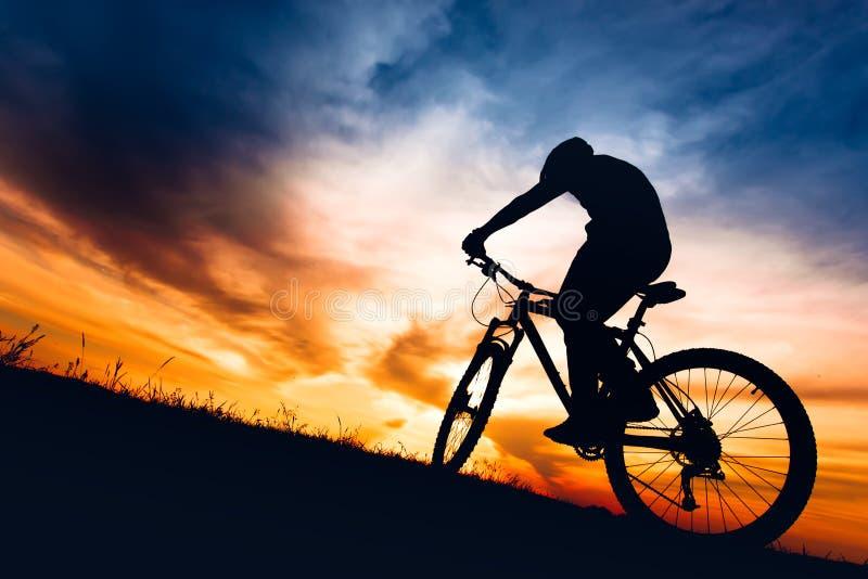 Silueta de la bici de montaña del montar a caballo del atleta en las colinas en la puesta del sol imagenes de archivo
