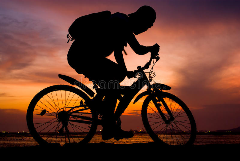 Silueta de la bici de montaña del paseo del backpacker foto de archivo