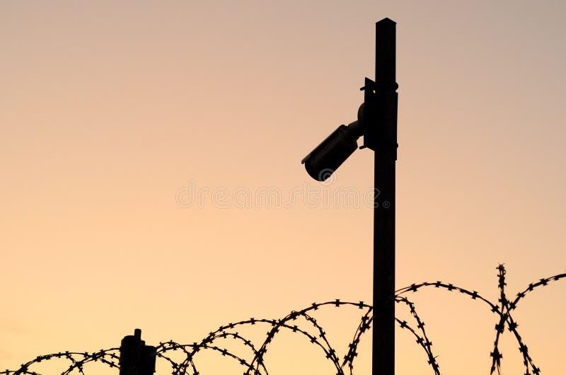 Silueta de la cámara de seguridad en el polo en puesta del sol Observación del perímetro del área protegida con de púas fotos de archivo