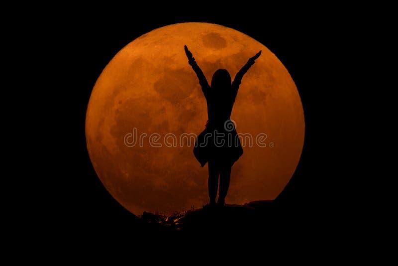 Silueta de la chica joven con la Luna Llena estupenda: éxito concentrado fotos de archivo libres de regalías