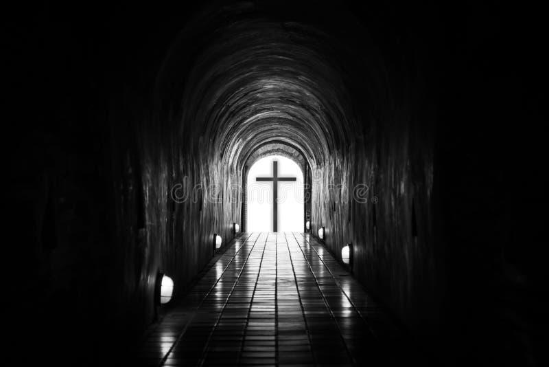 Silueta de la cruz en el extremo del túnel imagenes de archivo