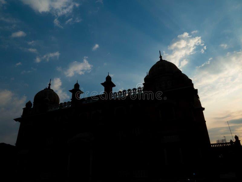 Silueta de la estructura antigua, de pájaros en cielo y de rayos solares imagen de archivo libre de regalías