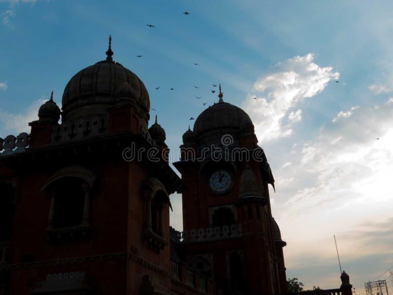 Silueta de la estructura antigua, de pájaros en cielo y de rayos solares fotografía de archivo