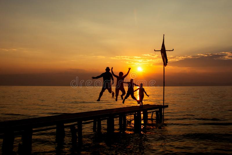 Silueta de la familia activa feliz que salta en puesta del sol del verano imagen de archivo