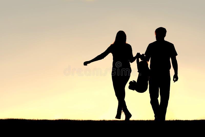 Silueta de la familia de tres personas que caminan en la puesta del sol foto de archivo libre de regalías