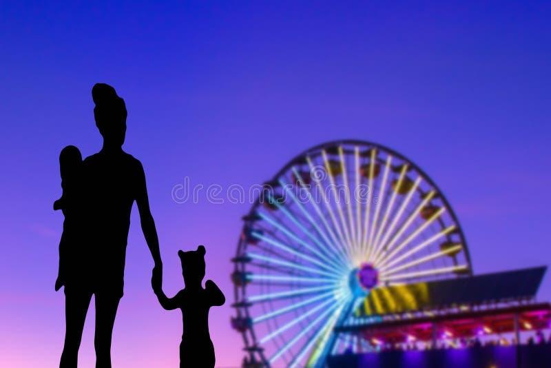 Silueta de la familia en un parque temático que mira a la madre de la noria con su pequeños hija y bebé foto de archivo