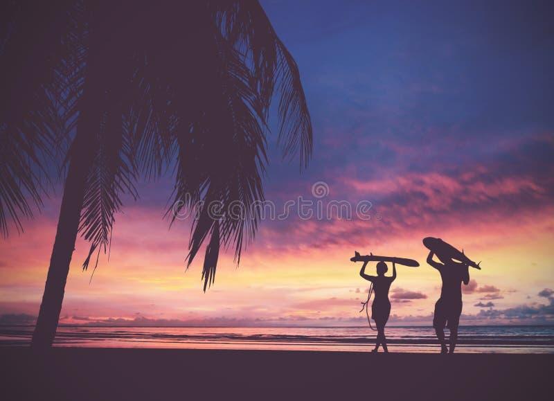 Silueta de la gente de la persona que practica surf que lleva su tabla hawaiana en la puesta del sol b foto de archivo libre de regalías