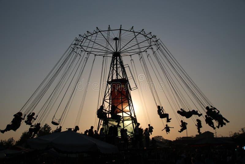 Silueta de la gente joven en la noria y el carrusel de balanceo en el movimiento de parada en fondo de la puesta del sol fotografía de archivo