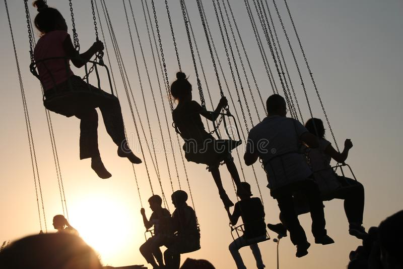 Silueta de la gente joven en la noria y el carrusel de balanceo en el movimiento de parada en fondo de la puesta del sol foto de archivo