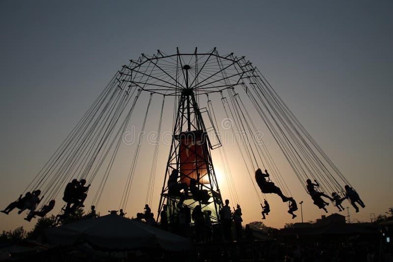 Silueta de la gente joven en la noria y el carrusel de balanceo en el movimiento de parada en fondo de la puesta del sol fotos de archivo