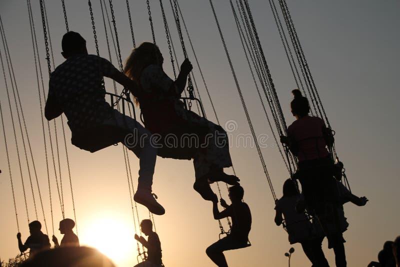 Silueta de la gente joven en la noria y el carrusel de balanceo en el movimiento de parada en fondo de la puesta del sol foto de archivo libre de regalías