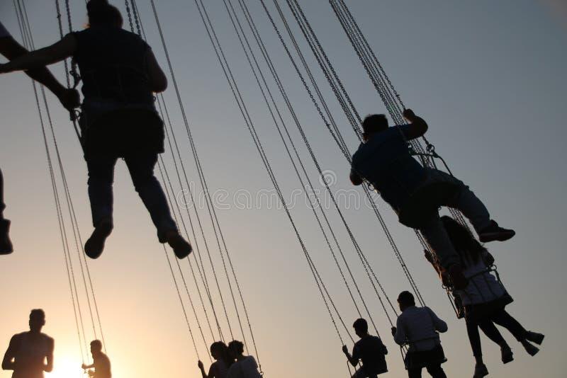 Silueta de la gente joven en la noria y el carrusel de balanceo en el movimiento de parada en fondo de la puesta del sol imágenes de archivo libres de regalías