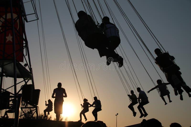Silueta de la gente joven en la noria y el carrusel de balanceo en el movimiento de parada en fondo de la puesta del sol imagen de archivo