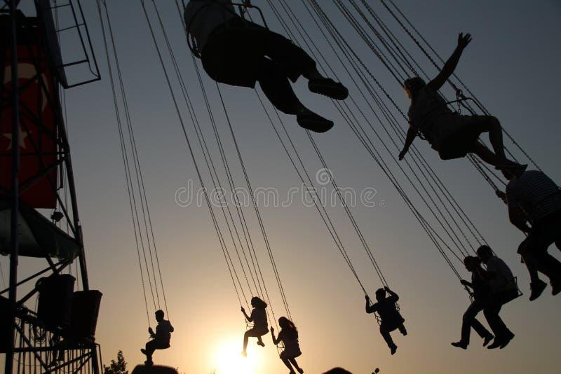 Silueta de la gente joven en la noria y el carrusel de balanceo en el movimiento de parada en fondo de la puesta del sol imagenes de archivo
