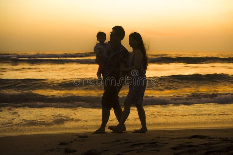 Silueta de la hija china asiática feliz y hermosa joven del bebé de la tenencia de la pareja que camina en la playa de la puesta  fotos de archivo
