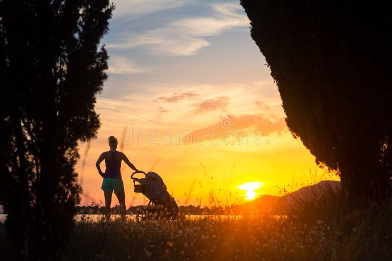 Silueta de la madre con el cochecito que disfruta de maternidad en la puesta del sol imagen de archivo