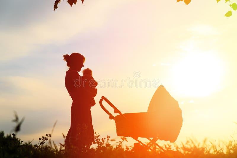 Silueta de la madre con el pequeño bebé en la puesta del sol imágenes de archivo libres de regalías
