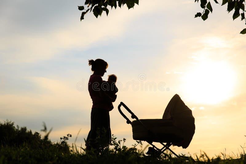 Silueta de la madre con el pequeños bebé y cochecito en el cielo imagen de archivo
