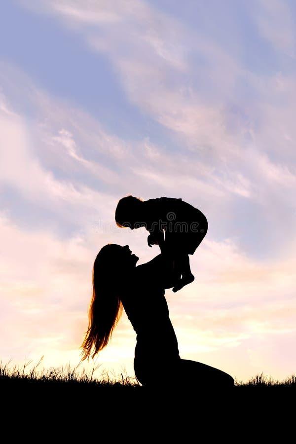 Silueta de la madre feliz que juega afuera con el bebé foto de archivo
