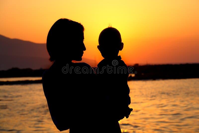 Silueta de la madre y del bebé fotos de archivo