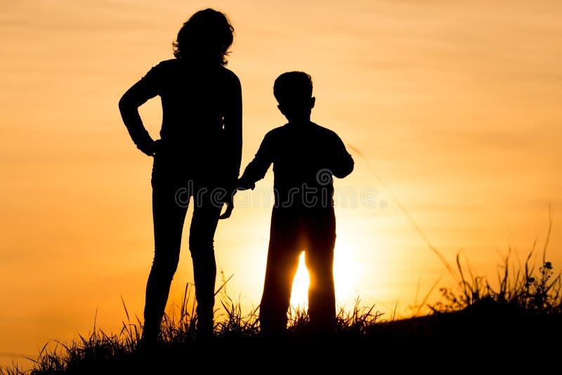 Silueta de la mamá y del hijo en los rayos de la puesta del sol foto de archivo libre de regalías