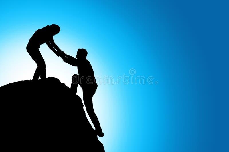 Silueta de la mano amiga entre el escalador dos imagen de archivo libre de regalías