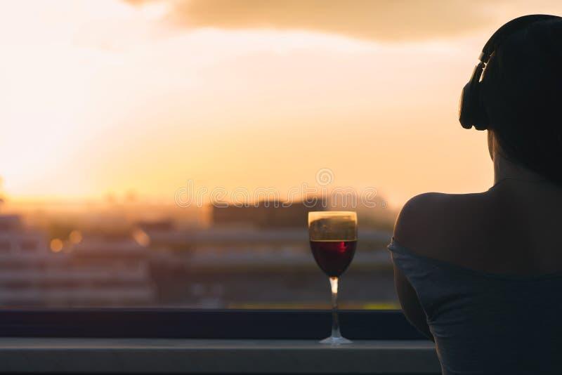Silueta de la mano femenina con el vidrio de vino rojo en el fondo de la ciudad de la puesta del sol foto de archivo libre de regalías